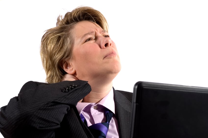 A business woman grabbing her neck in pain. She's worked to long and hard on the laptop.