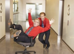 Businessman pushing co-worker in chair in corridor