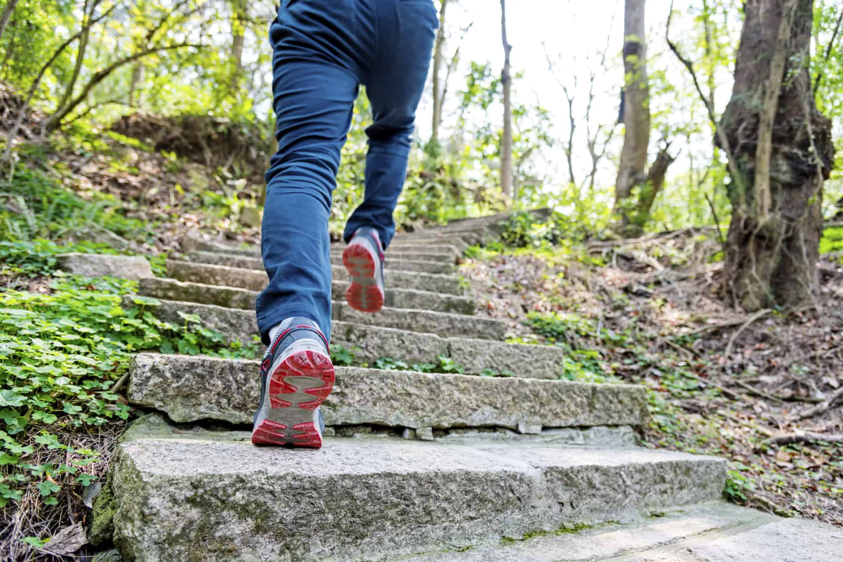 Low section of man running on forest stairs in China.
